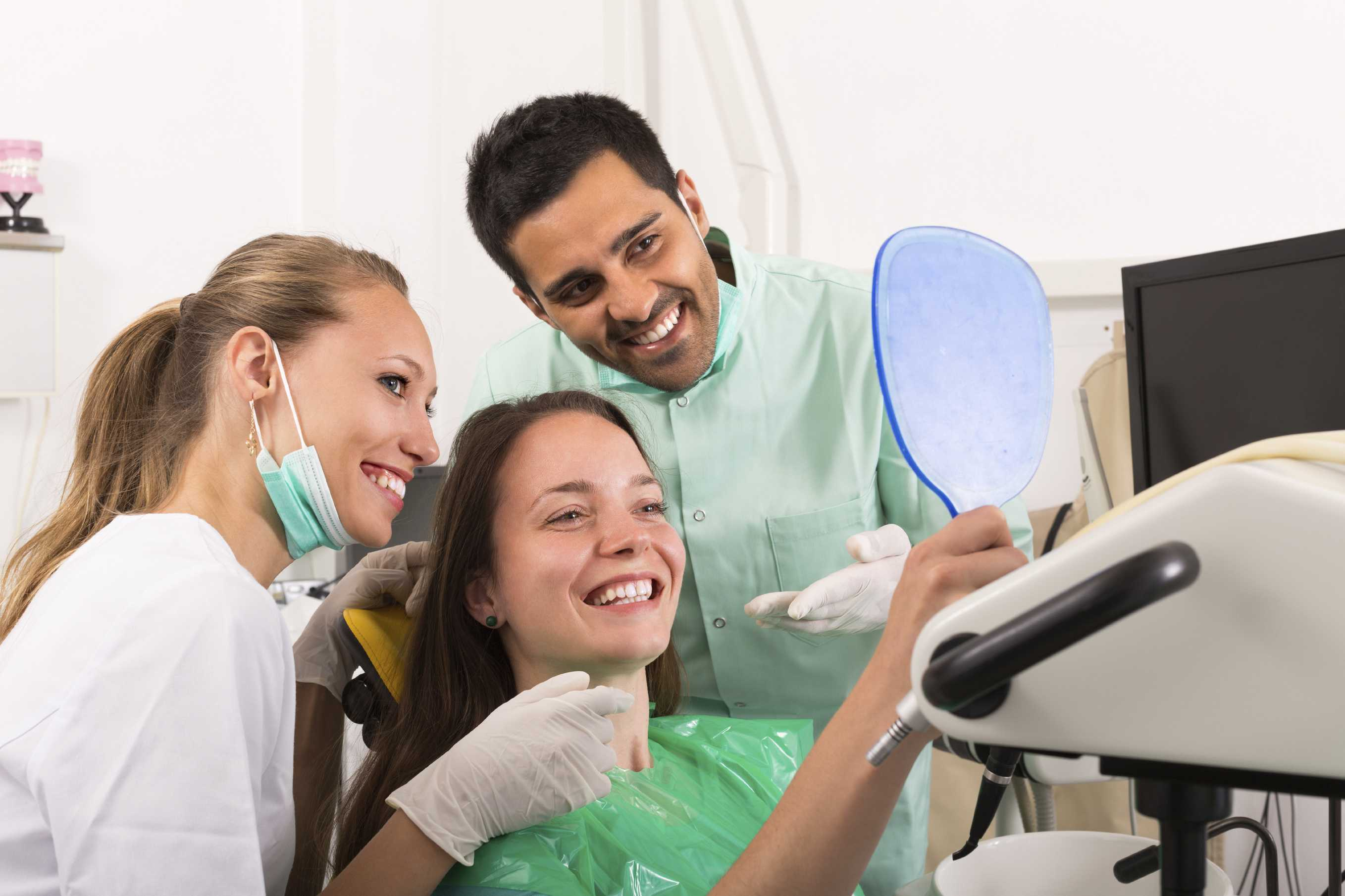 Smiling dentist with assistant and contented patient looking in mirror at dental clinic